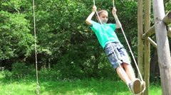 Smiling boy swinging on a rope at a playground Stock Footage