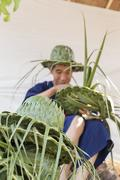 Artisan weaving palm leaf for making hat Stock Photos