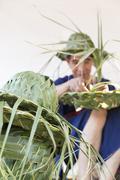 Artisan weaving palm leaf for making hat Stock Photos