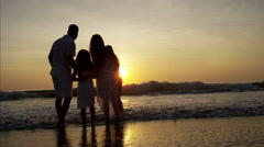 Silhouette of Latin American family on the beach holiday at sunrise Stock Footage