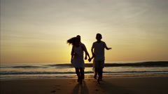 Silhouette of active Spanish family having fun on the beach at sunrise Stock Footage