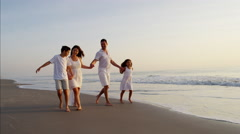 Happy Spanish family walking on the beach vacation at sunset Stock Footage