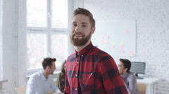 Happy hipster looking at camera standing in office Arkistovideo