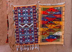 Colorful Moroccan Berber carpets hanging on adobe wall - stock photo