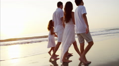 Spanish children spending leisure time with parents by ocean at sunset Stock Footage