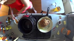 Young girl put piece of frying meat from pan to slow cooker Stock Footage