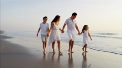 Spanish parents in white clothing enjoying time with children by ocean at sunset Stock Footage