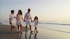 Spanish children spending leisure time with parents by ocean at sunrise Stock Footage