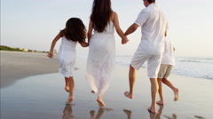 Young Hispanic family in white clothing walking together on the beach Stock Footage