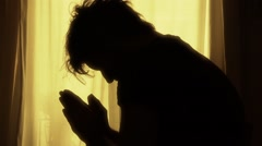 Silhouette Of Man Praying At Home During The Day Stock Footage