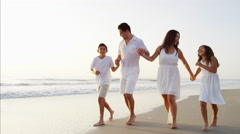 Attractive Spanish family in white clothing having fun on the beach holiday Stock Footage