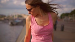 Beautiful brunette girl in pink dress standing on Moscow river embankment. Slow Stock Footage