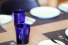 Dish, spoon, fork and blue glass on wooden table, blur and defocus Stock Photos