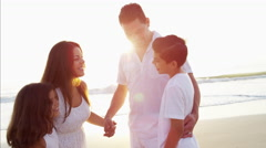 Attractive Latin American family in white clothing relaxing on the ocean beach Stock Footage