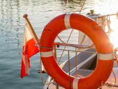 lifebuoy on sailboat and polish ensign - stock photo