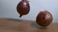 Two onions bounce in slow motion onto a cutting board - dutch shot Stock Footage