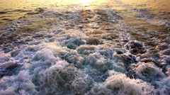Sea Waves Bubbles and Sunset Behind Ferryboat Stock Footage