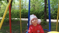 Girl child swinging on a swing. Girl holding a large orange balloon. Stock Footage