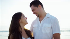 Beautiful Latin American couple enjoying time together on the beach outdoors Stock Footage