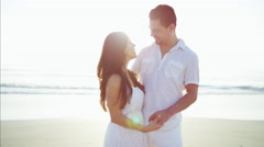 Portrait of beautiful Latin American couple enjoying Summer holiday on the beach Stock Footage