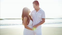 Young Latin American man and woman smiling together on beach outdoors Stock Footage