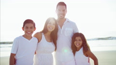 Portrait of Hispanic family enjoying Summer and waving hands on the beach Stock Footage