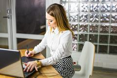 Young female designer using graphics tablet while working with computer - stock photo