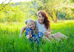 Little Girl and Mom Picking Apples. Portrait of happy mother and young daughter Stock Photos