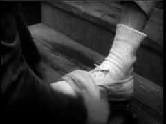 Shoe shine man slipping note into person's sock, 1961 - stock footage