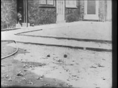 Dog carrying collar coming out of house into yard, 1920s - stock footage