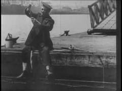 Fisherman sitting at edge of pier reeling in his catch, 1920s Stock Footage