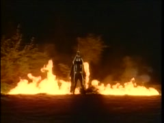 Person in skeleton costume with sword above head in front of flames, 1980s Stock Footage