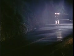 Car speeding down mountain road in the rain at night, 1970s Stock Footage