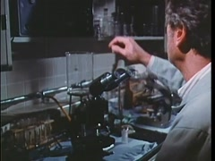 Scientist viewing animal cells on computer screen in lab, 1970s Stock Footage