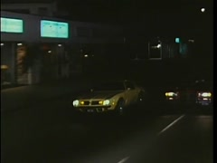 Car trying to run another car off  the road at night, 1970s Stock Footage