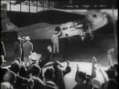 Panning shot of people waving at vintage aircraft during take off, 1930s Stock Footage