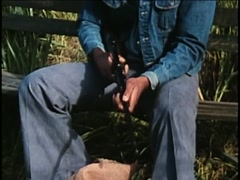 Man in denim jacket sitting on bench assembling rifle, 1970s Stock Footage