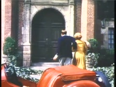 Rear view of couple hurrying into brick house, 1950s Stock Footage