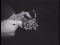 Close-up of man trying to open padlock with skeleton keys, 1950s Stock Footage