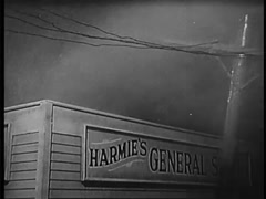 Electricity pylon falling on car parked by store during rain storm, 1940s - stock footage