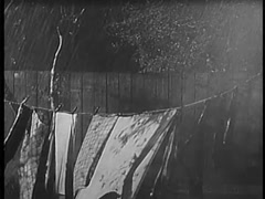 Garments on clothesline getting soaked during rainstorm, 1940s Stock Footage