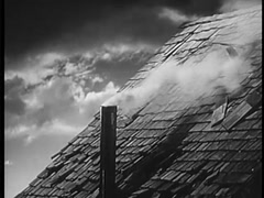 Close-up of chimney emitting smoke on roof of house as clouds pass by, 1940s - stock footage