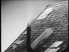 Roof of house with smoke coming out of chimney, 1940s - stock footage