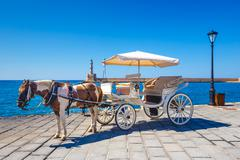 Horse carriage for transporting tourists in old port of Chania on Crete, Gree Stock Photos