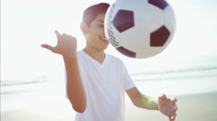 Portrait of young Latin American boy playing on beach vacation with soccer ball Stock Footage