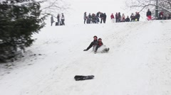 Family Fun Snow Sliding Down Parc Buttes Chaumont During Winter, Paris Stock Footage