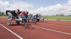 4K Disabled wheelchair athletics team competing in a race at race track Stock Footage