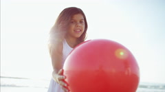 Cute smiling Hispanic girl playing on beach vacation with red ball Stock Footage