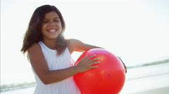 Portrait of beautiful Latin American girl playing on beach holiday with red ball Stock Footage