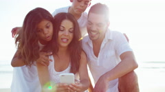 Young Spanish family taking a photo on smartphone on the beach Stock Footage